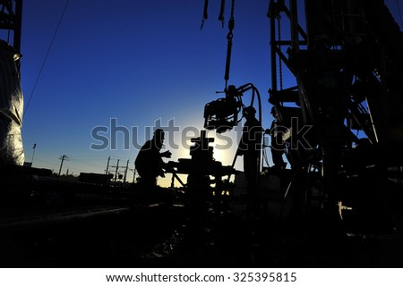 Oil field oil workers at work - stock photo