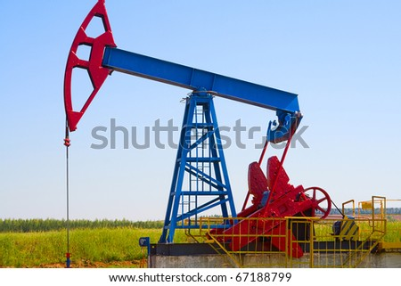 Oil field Pump Jack with a bright blue sky - stock photo
