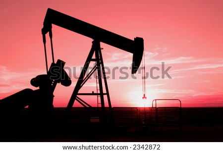 Oil field pump jack with setting sun in background - stock photo