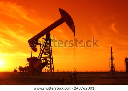 Oil field scene, beam pumping unit silhouette, very beautiful - stock photo
