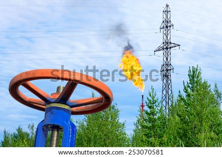 Oil field. The valve with a gas torch on a background. - stock photo