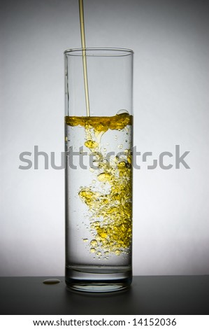 Oil flows in a vase with water - stock photo