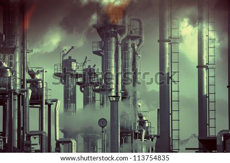 oil, gas and fuel industry, pollution and toxic clouds. focal point on the pipes close to the clock. - stock photo