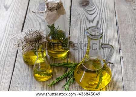 Oil in a bottle and fresh organic rosemary on wood table - stock photo