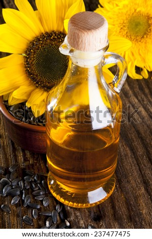 Oil in bottle with sunflowers on wooden background - stock photo