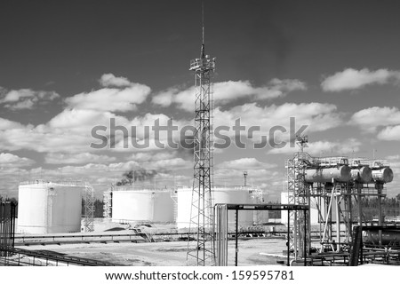 Oil industry and gas industry. Work of refinery petrochemical plant. Oil reservoir and storage tank of mineral oil. Flame torch. Black and white photo - stock photo