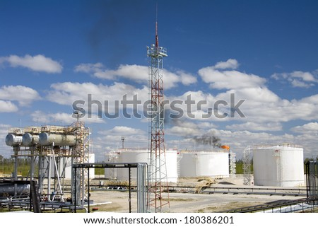 Oil industry and gas industry. Work of refinery petrochemical plant. Oil reservoir and storage tank of mineral oil. Flame torch. - stock photo