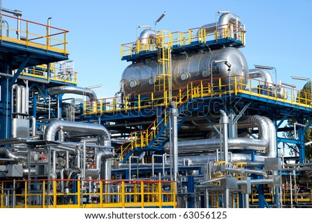 Oil industry equipment installation, metal pipes and tanks - stock photo