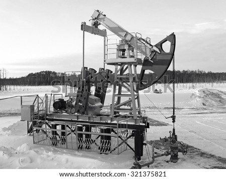 Oil industry. Industrial construction and mechanism. Winter oil field. Black and white photo - stock photo