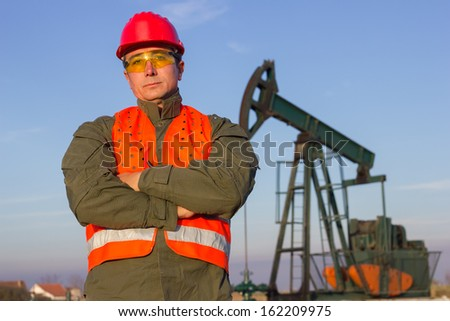 Oil Industry Pump jack with one oil worker.
