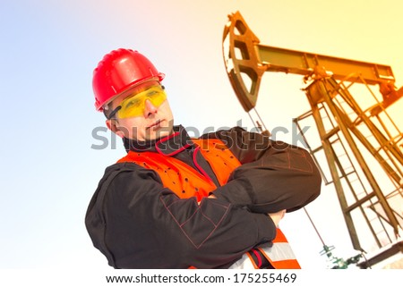 Oil Industry Pump jack with one oil worker,best focus helmet and vest, soft focus pump,lens flare, flaring  - stock photo