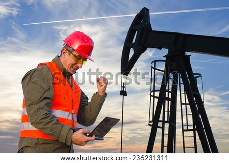 Oil Industry Pump jack with one oil worker who using a laptop.