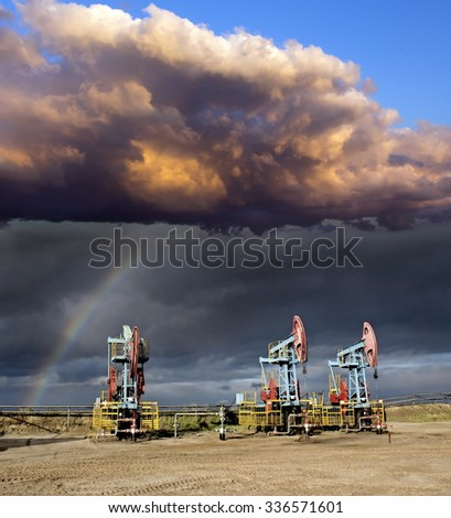 Oil industry. Storm and rainbow over oil pumps. Oil field. Gas industry. - stock photo