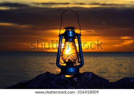 oil lamp on the beach at sunrise . - stock photo