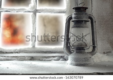 oil lamp on winter sill and lights in home