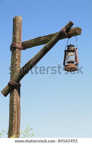 oil lamp on wooden post - stock photo
