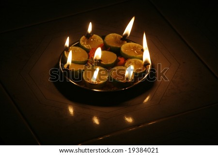 Oil lamps sit on a tray at a temple. - stock photo