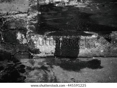 Oil leaked on opened old and dirty concrete manhole cover on pavement, black and white effect