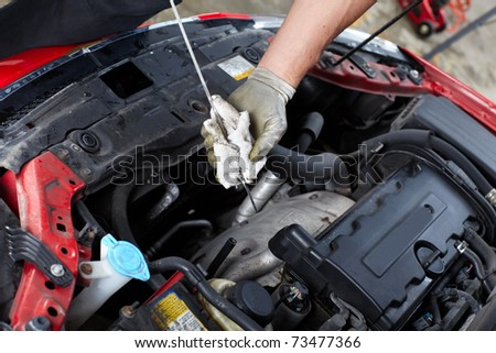 Oil level checking. Mechanic in auto repair shop. - stock photo