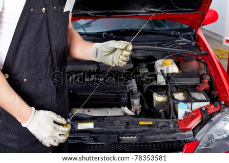 Oil level checking. Mechanic in auto repair shop.