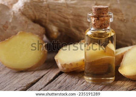 oil of ginger in a glass bottle with cork macro on an old table horizontal - stock photo