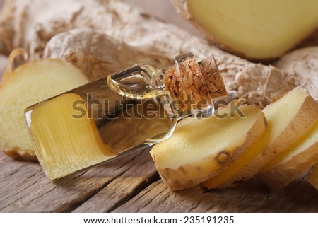oil of ginger in a small glass bottle on a table close-up, horizontal - stock photo