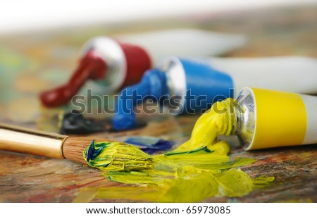 Oil paint tubes and pain brush over colorful artist's palette - stock photo