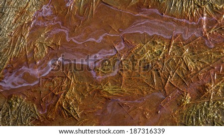 Oil patterns flowing in a natural wetland with grass and sand. - stock photo