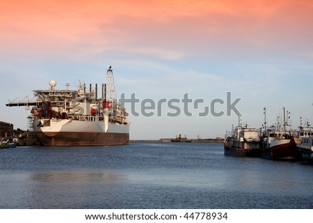 Oil processing ship and fishing boats in a habor - stock photo