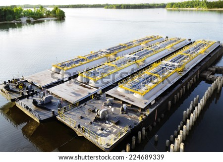Oil product tanker barges on the river - stock photo