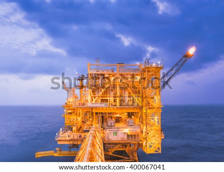 Oil production platform with full yellow lights during sunset. - stock photo