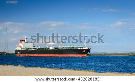 Oil products tanker heading to the port through canal - stock photo