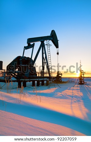 Oil pump against the rising sun. Western Siberia - stock photo