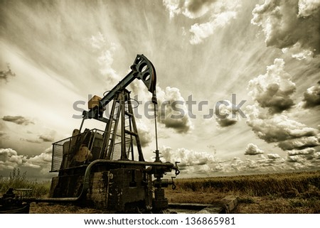 Oil pump, industrial machine for petroleum in the sunset background - stock photo