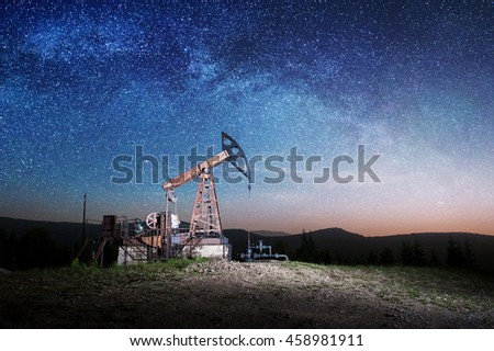Oil pump is working on the oil field. Oil industry equipment. Starry Sky shines above - stock photo