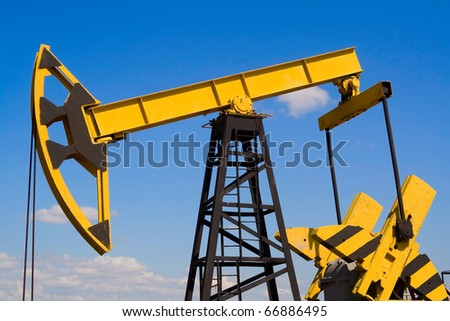 Oil pump jack against bright, blue sky - stock photo