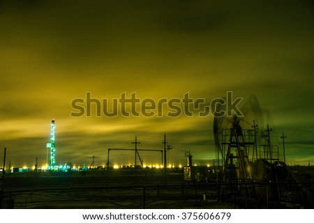 Oil pump jack and drilling rig at the night sky background. Long exposure. - stock photo