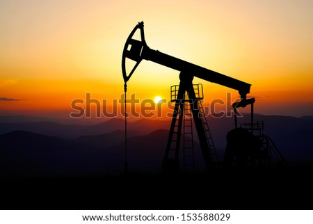 oil pump jack bringing energy for world in a beautiful sunset - stock photo