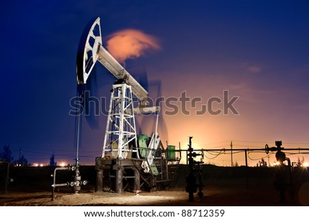 Oil pump-jack in action. Gas torches. Night view. Long exposure.