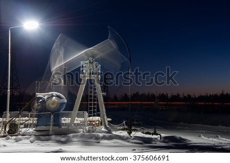 Oil pump-jack in action. Night view. Long exposure.
