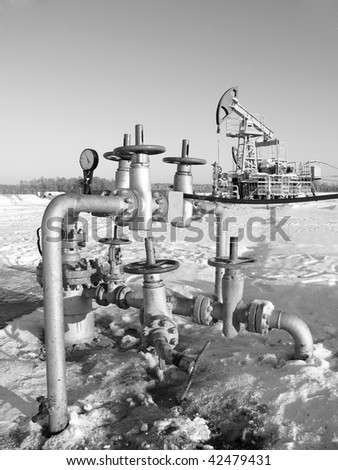 Oil pump jack in work. Oil industry in West Siberia. Siberian frost in sunny day. - stock photo