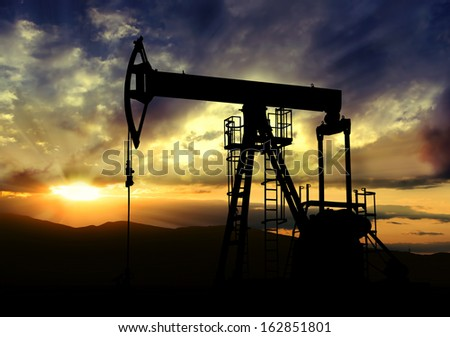 Oil pump jack.Oil industry equipment on sunset background - stock photo