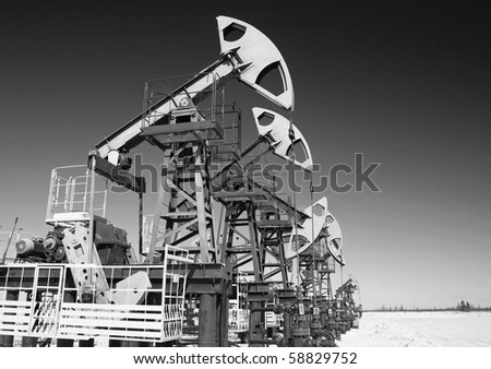 Oil pump jack on a sand. Black and white photo - stock photo