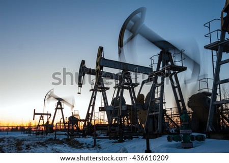 Oil pump jacks group and wellhead with valve armature during sunset on the oilfield. Oil and gas concept.