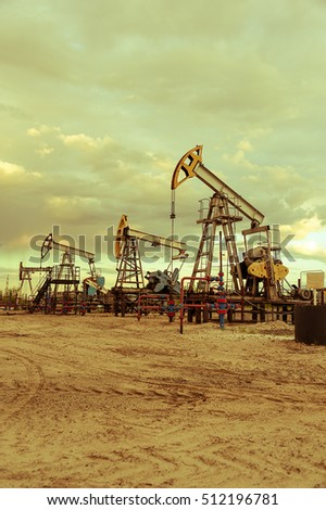 Oil pump jacks group and wellhead with valve armature during sunset on the oilfield. Oil and gas concept. Dramatic cloudy sky background. Toned.