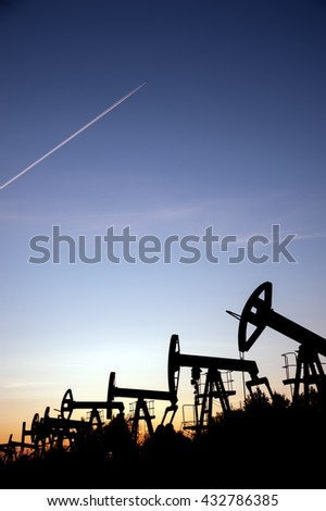 Oil pump jacks on a oilfield and airplane contrail at sunset sky background. Concept oil and gas industry.