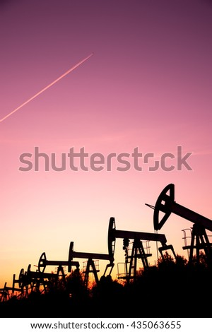 Oil pump jacks on a oilfield and airplane contrail at sunset sky background. Concept oil and gas industry. - stock photo