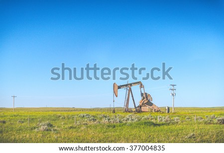 Oil Pump Oil Rig Energy in countryside with blue sky background.  - stock photo