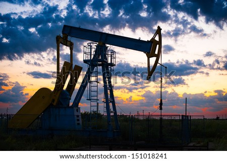 Oil pump oil rig energy industrial machine for petroleum in the sunset/sunrise background for design - stock photo