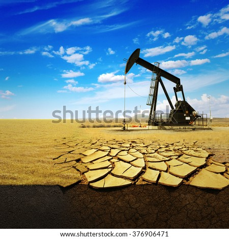Oil pump oil rig energy industrial machine for petroleum on the background of dry earth with cracks. Concept Ecology - stock photo